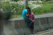 I took this while we were driving down the highway. These 2 kids were hanging out on the center divide. Speed limit is probably 60 kph, about 37 mph (or faster!) It's funny but people wait all along the road for the bus and cross anywhere they want, even without an overpass.