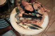 A plate full of mackerel steaks on a butterflied chunk of needle fish.